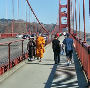 Zen Buddhist nun and Theravada Buddhist monk in lively conversation, Golden Gate Bridge.